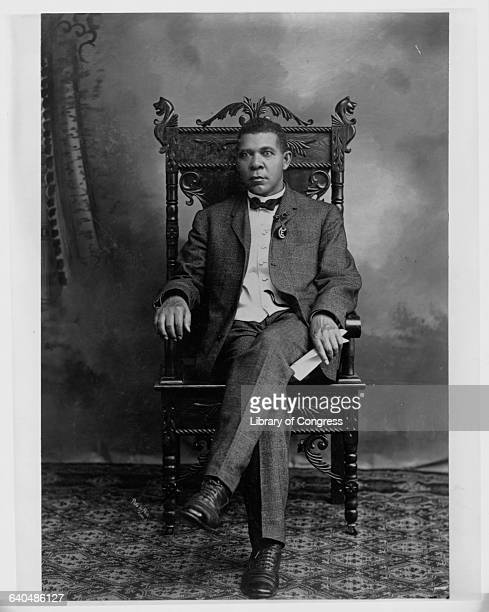 Booker T Washington seated in a chair 1904