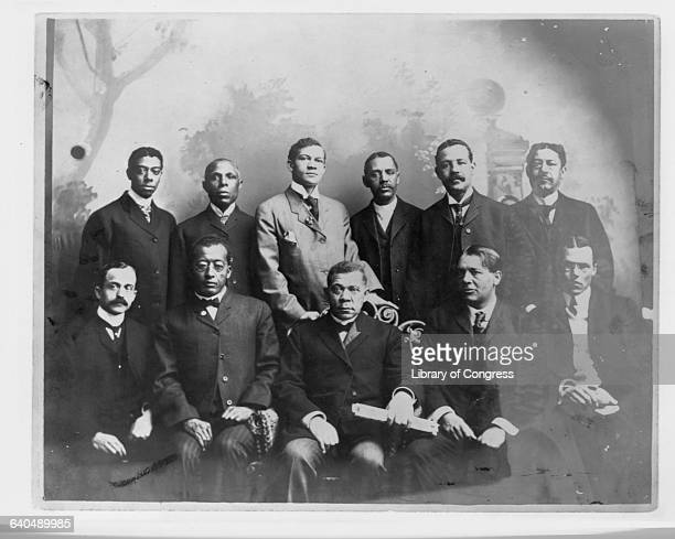 Booker T Washington seated with a group of 11 men