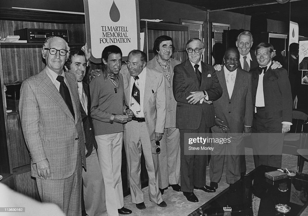 Booking agent Willard Alexander (1908-1984), Vice President of Sherwood Packaging Floyd Glinert, U.S. jazz drummer Buddy Rich (1917-1987), U.S. jazz musician Woody Herman (1913-1987), businessman Tony Martell, U.S. jazz musician Benny Goodman (1909-1986), U.S. jazz pianist Count Basie (1904-1984), U.S. jazz pianist Stan Kenton (1911-1979) and U.S. jazz singer Mel Torme (1925-1999) gather beneath a sign which reads 'T.J. Martell Memorial Foundation', in New York, USA, circa 1975.