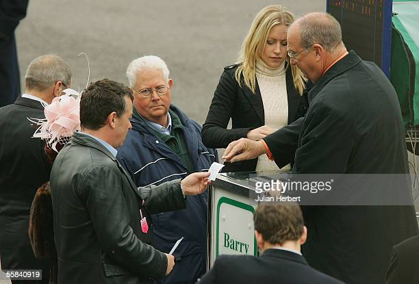 Bookmaker Barry Dennis takes a bet from actors Shane Richie during filming of an episode of 'EastEnders' at Windsor Racecourse on October 3 2005 in...