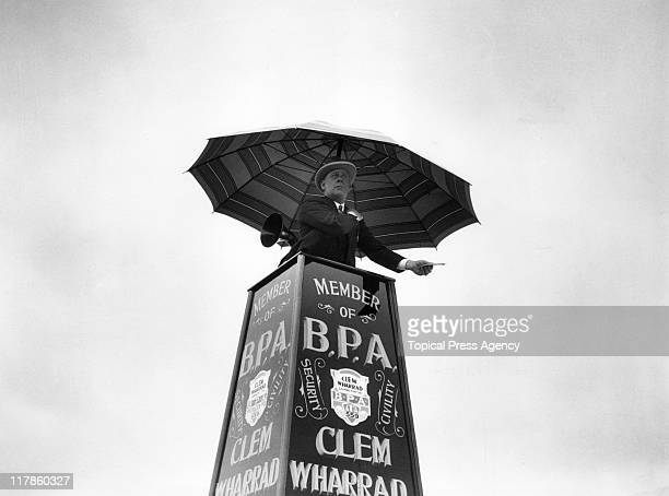 Bookmaker Clem Wharrad, sheltered by an umbrella, issuing tic-tac signals during the Derby meeting, from his tower at Epsom racecourse in Epsom,...