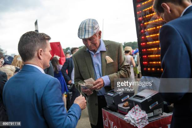 A bookmaker counts money at Royal Ascot at Ascot Racecourse on June 22 2017 in Ascot England The fiveday Royal Ascot meeting is one of the highlights...