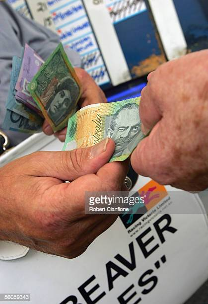 A bookmaker exchanges money with a better in the betting ring during The Crown Oaks Day at Flemington Racecourse November 3 2005 in Melbourne...