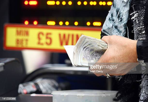 A bookmaker holds onto cash as she takes bets on Champion Day at the Cheltenham Festival 2012 on March 13 2012 in Cheltenham England Tens of...