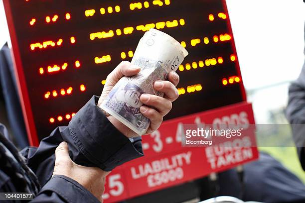 A bookmaker holds UK twenty pound bank notes at Ascot racecourse in Ascot UK on Friday Sept 24 2010 British horseracing will host a new 13...