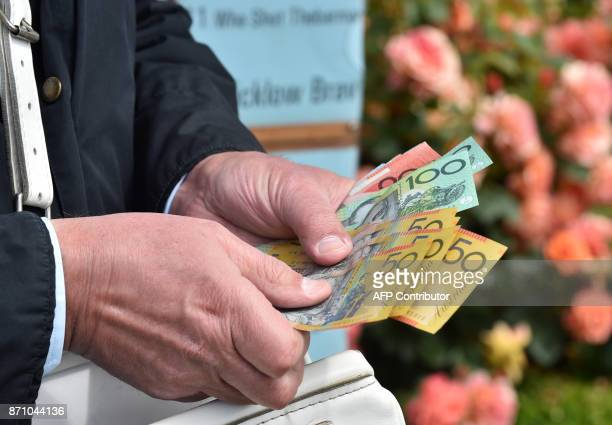 A bookmaker prepares for the first race of the day ahead of Australia's premier horse race the 157th Melbourne Cup at Flemington Racecourse in...
