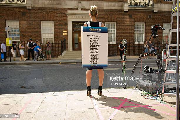 A bookmaker presents the latest odds on boys names outside the Lindo Wing of St Mary's Hospital in London on July 17 where Prince William and his...