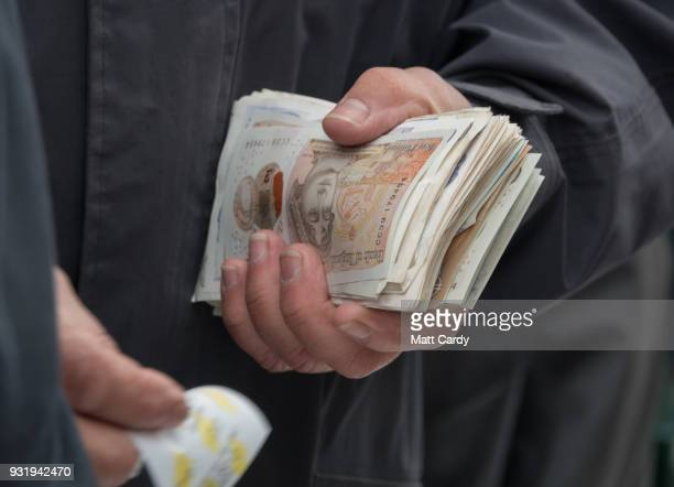 A bookmaker takes bets ahead of the Queen Mother Champion Steeple Chase on Ladies Day at the Cheltenham Racecourse on March 14 2018 in Cheltenham...
