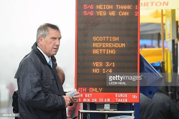 A bookmaker takes bets on a 'Referendum Race' sponsored by the bookmakers Ladbrokes at Musselburgh racecourse in Edinburgh Scotland on September 15...