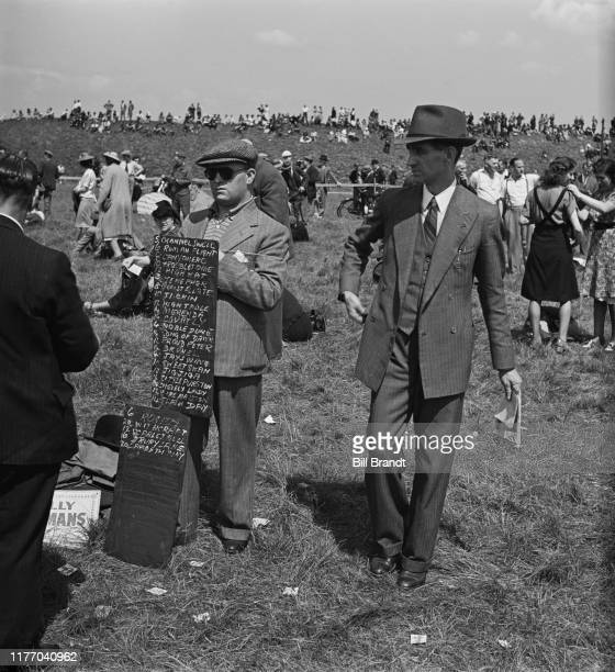 A bookmaker with his chalked tote board displays the betting odds for the wartime New Derby run at Newmarket racecourse in Suffolk 18th June 1941...