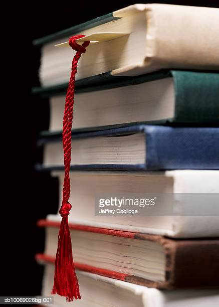 Bookmark dangling from stack of books, close-up