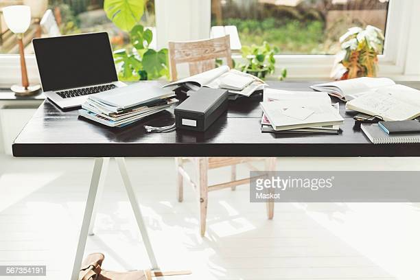 Books and laptop on table in home office