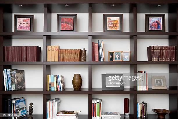 books and picture frames in shelves - urn stock pictures, royalty-free photos & images
