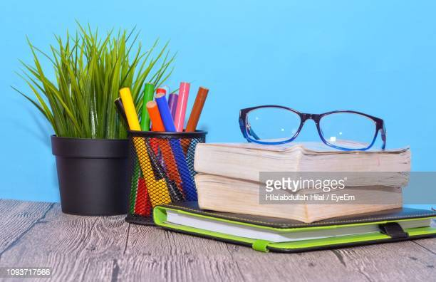 books and potted plant against blue wall on table - hilal stock photos and pictures