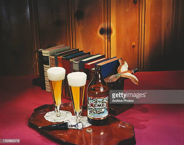 Books behind beer glasses and beer bottle