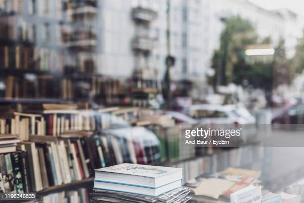 books in store seen from glass window - shop window stock pictures, royalty-free photos & images