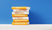 Books of Compliance And Regulations In Front Grey Wall