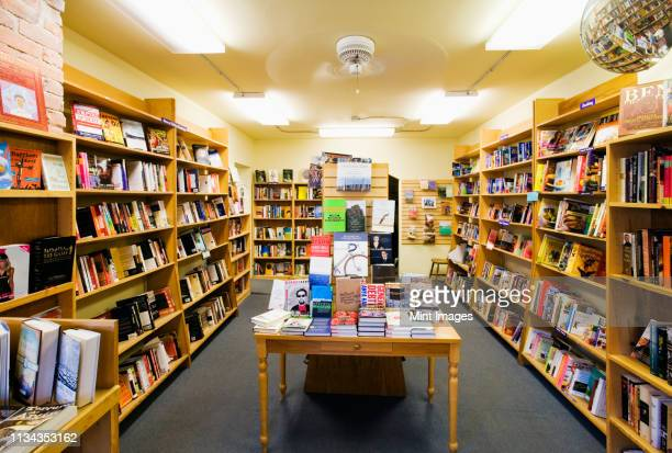 books on shelves and table in bookstore - book shop stock pictures, royalty-free photos & images