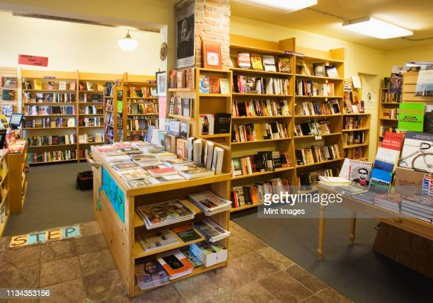 books on shelves and tables in bookstore - book shop stock pictures, royalty-free photos & images