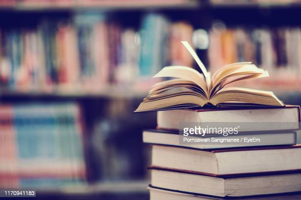 books on table against shelf in library - boek stockfoto's en -beelden