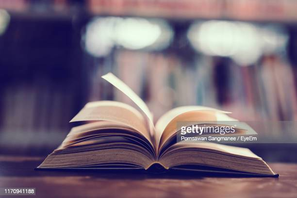 books on table against shelf in library - literature stock pictures, royalty-free photos & images