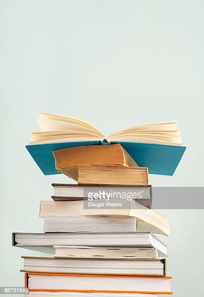 books piled up. - stack of books stock photos and pictures