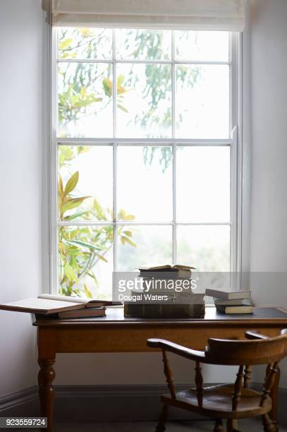 Books stacked on a vintage library writing desk beside window.