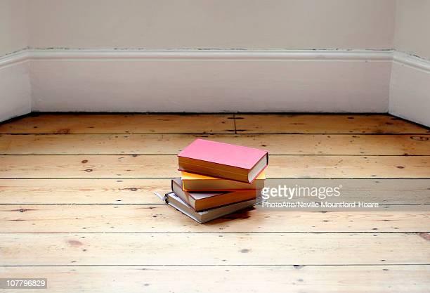 Books stacked on hardwood floor