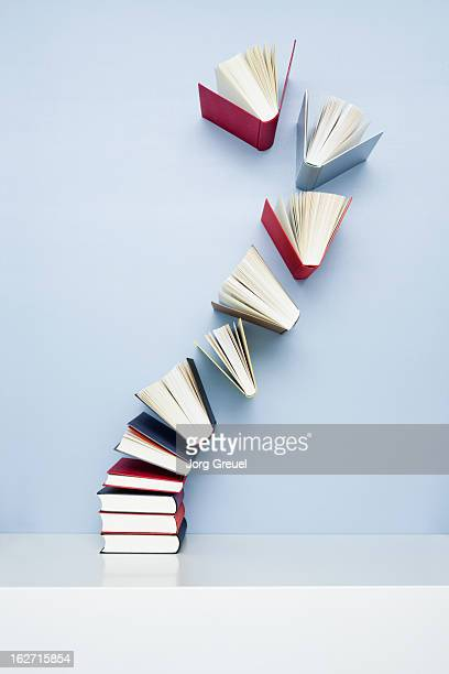 books taking off from a stack - boek stockfoto's en -beelden