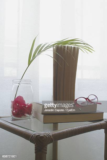 Books With Eyeglasses On Table By Window At Home
