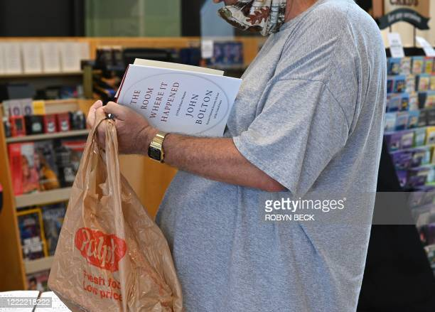 "Bookstore customer looks through a copy of the new book ""The Room Where it Happened"" by former US National Security Advisor John Bolton, at Barnes &..."