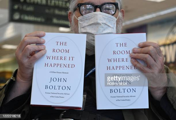 "Bookstore customer Thomas O'Shaughnessy holds up two copies of the new book he will buy, ""The Room Where it Happened"" by former US National Security..."