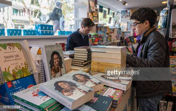 Bookstore owner Ricardo Gomes and a customer are seen behind copies of Portuguese and English editions of 'Becoming' a memoir by former US First Lady...