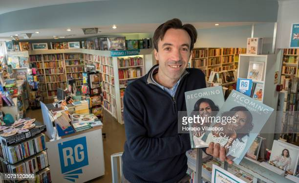 Bookstore owner Ricardo Gomes holds copies of the Portuguese and English editions of 'Becoming' a memoir by former US First Lady Michelle Obama at...