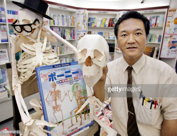 Bookstore sales clerk Koki Sato displays a papercraft book Bony and its completed model of lifesize skeleton 160cm in height and weighing only 250g...