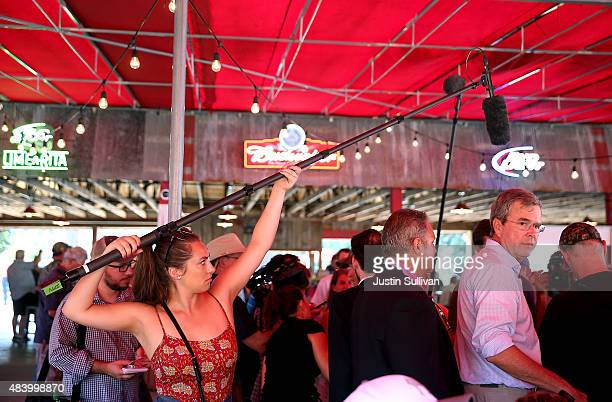 A boom microphone operator follows republican presidential hopeful and former Florida Gov Jeb Bush as he greets fairgoers during the Iowa State Fair...