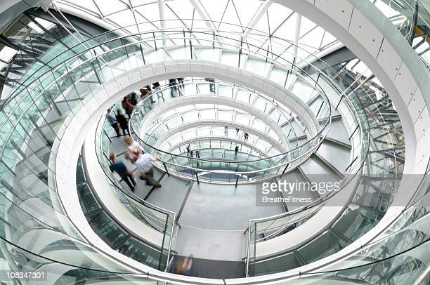 Boom shot of endless spiral staircase with glass handrail