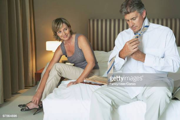 Boomer couple dresses in hotel room