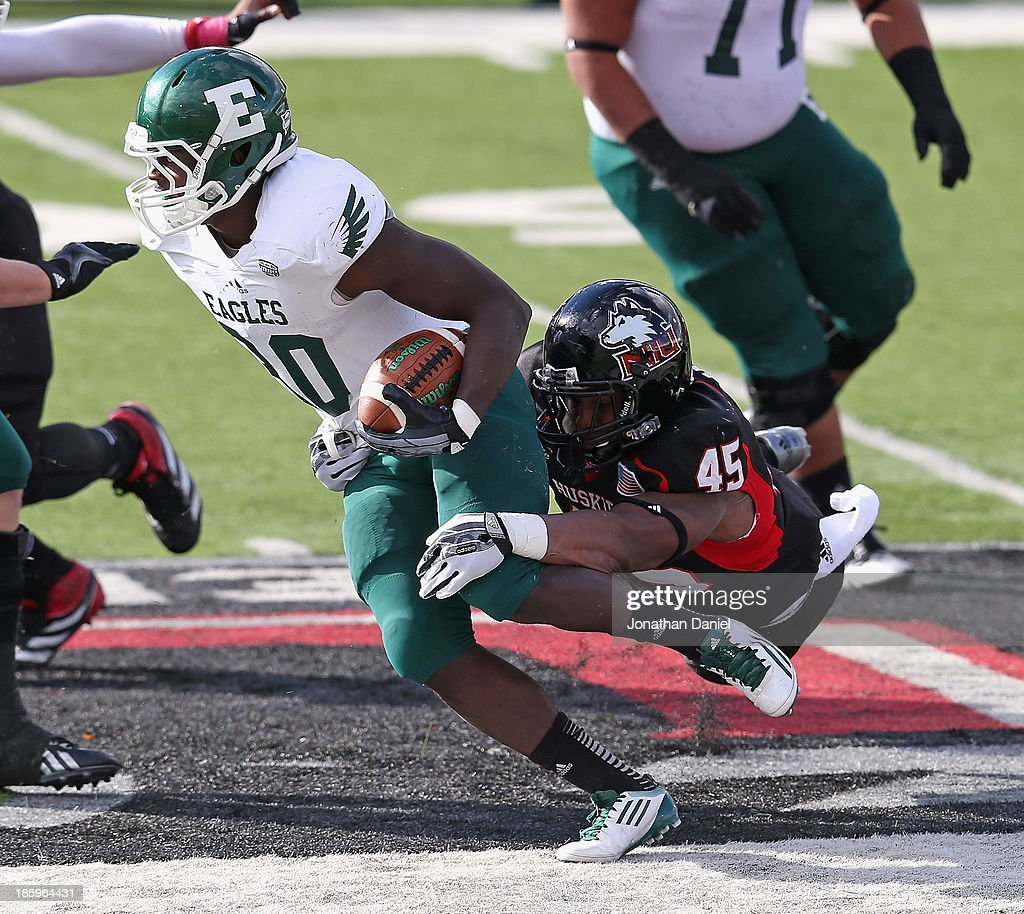 Boomer Mays #45 of the Northern Illinois Huskies tackles Bronson Hill #30 of the Eastern Michigan Eagles at Brigham Field on October 26, 2013 in DeKalb, Illinois. Northern Illinois defeated Eastern Michigan 59-20.