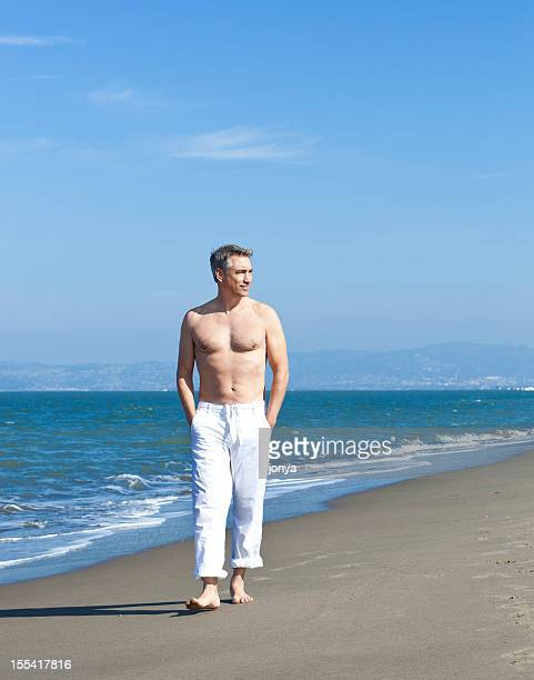 boomer walking along the beach barechested - handsome 50 year old men stock photos and pictures