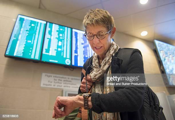 Boomer woman checking time at airport