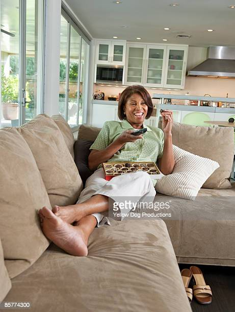 Boomer Woman Watching TV and Eating Chocolates