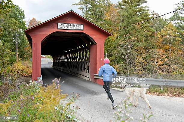 boomer women running with dog - covered bridge stock pictures, royalty-free photos & images