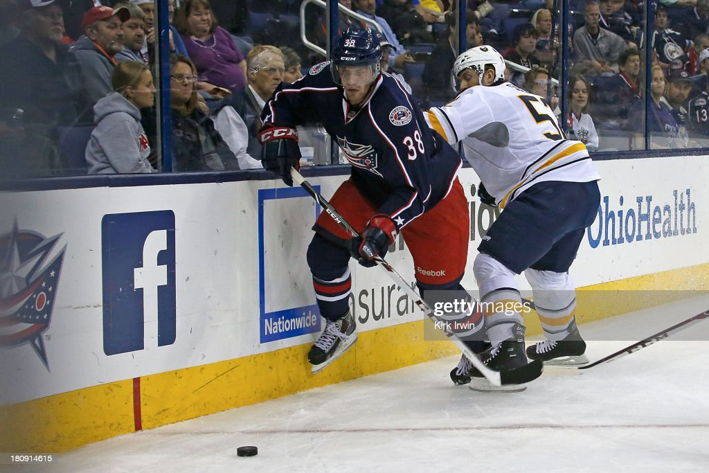 Boone Jenner #38 of the Columbus Blue Jackets and Alexander Sulzer #52 of the Buffalo Sabres battle for control of a loose puck on September, 2013 at Nationwide Arena in Columbus, Ohio. Buffalo defeated Columbus 3-1.