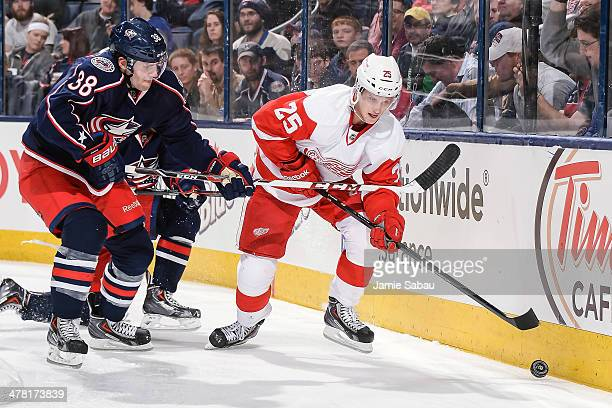Boone Jenner of the Columbus Blue Jackets and Cory Emmerton of the Detroit Red Wings battle for control of the puck on March 11 2014 at Nationwide...