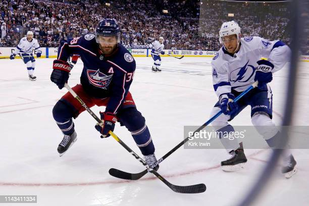 Boone Jenner of the Columbus Blue Jackets and Jan Rutta of the Tampa Bay Lightning chase after a loose puck in Game Four of the Eastern Conference...