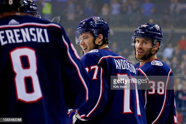 Boone Jenner of the Columbus Blue Jackets and Zach Werenski congratulate Josh Anderson after he scored an empty net goal during the game against the...