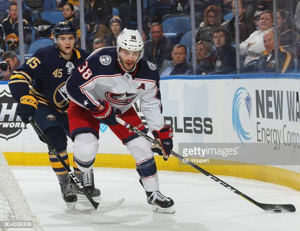 Boone Jenner of the Columbus Blue Jackets beats Brendan Guhle of the Buffalo Sabres to the puck during the second period of an NHL game on January 11...