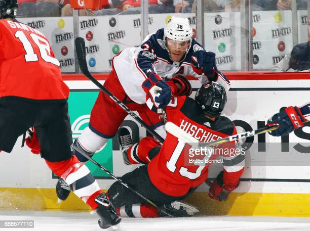 Boone Jenner of the Columbus Blue Jackets checks Nico Hischier of the New Jersey Devils during the first period at the Prudential Center on December...