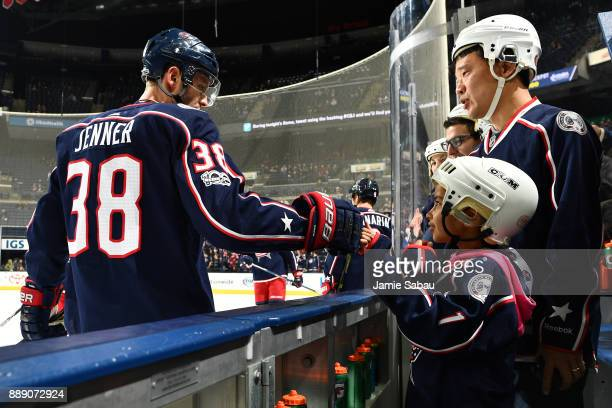 Boone Jenner of the Columbus Blue Jackets high fives a fan during pregame warmups prior to the start of the game against the Arizona Coyotes on...